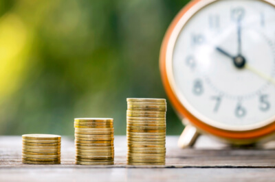 Gold money coins and alarm clock - business success concept
